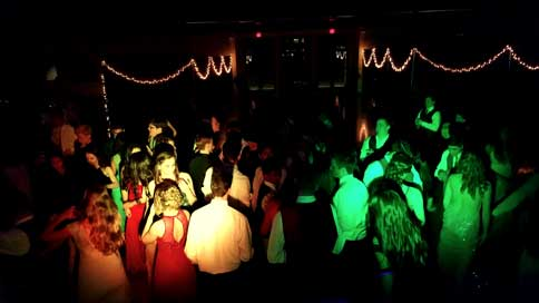 A picture taken at a high school prom. There are multi-color lights creating a colorful green and yellow haze on the dance floor full of students and there are white Christmas lights outlining the walkway leading up to the dance floor.