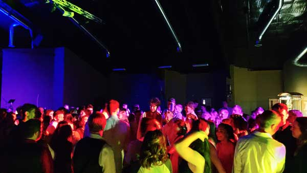 An image of a high school prom taken from the perspective of the DJ who is setup along the side of the dance floor. There are about 100 students dancing and you can see the yellow, purple, and red colors from the effect lighting casting a tinted shadow onto the dancing students.