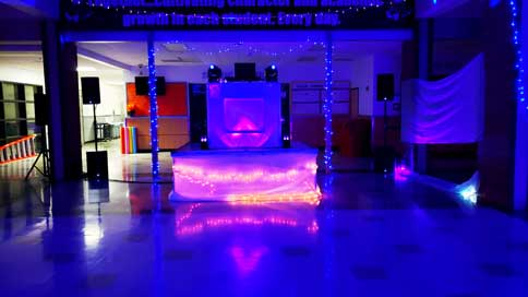 An image take of the dance floor for a high school dance. There is a blue color tone cast onto the room and dance floor due to the multiple lighting fixtures spread throughout the dance floor area. The DJ booth is centered at the front of the dance floor on a small stage that rises up off the floor about 2 feet.