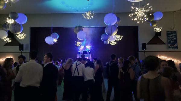 An image of a high school prom. The picture is taken from the back of the dance floor. There are about 100 students dancing and there are baloons and special twinkling lights handing from the tall ceiling of the school's common area. At the very front of the dance floor, on the stage you can see the setup for DJ Harris with some effects lighting casting a blue shadow out into the crowd.