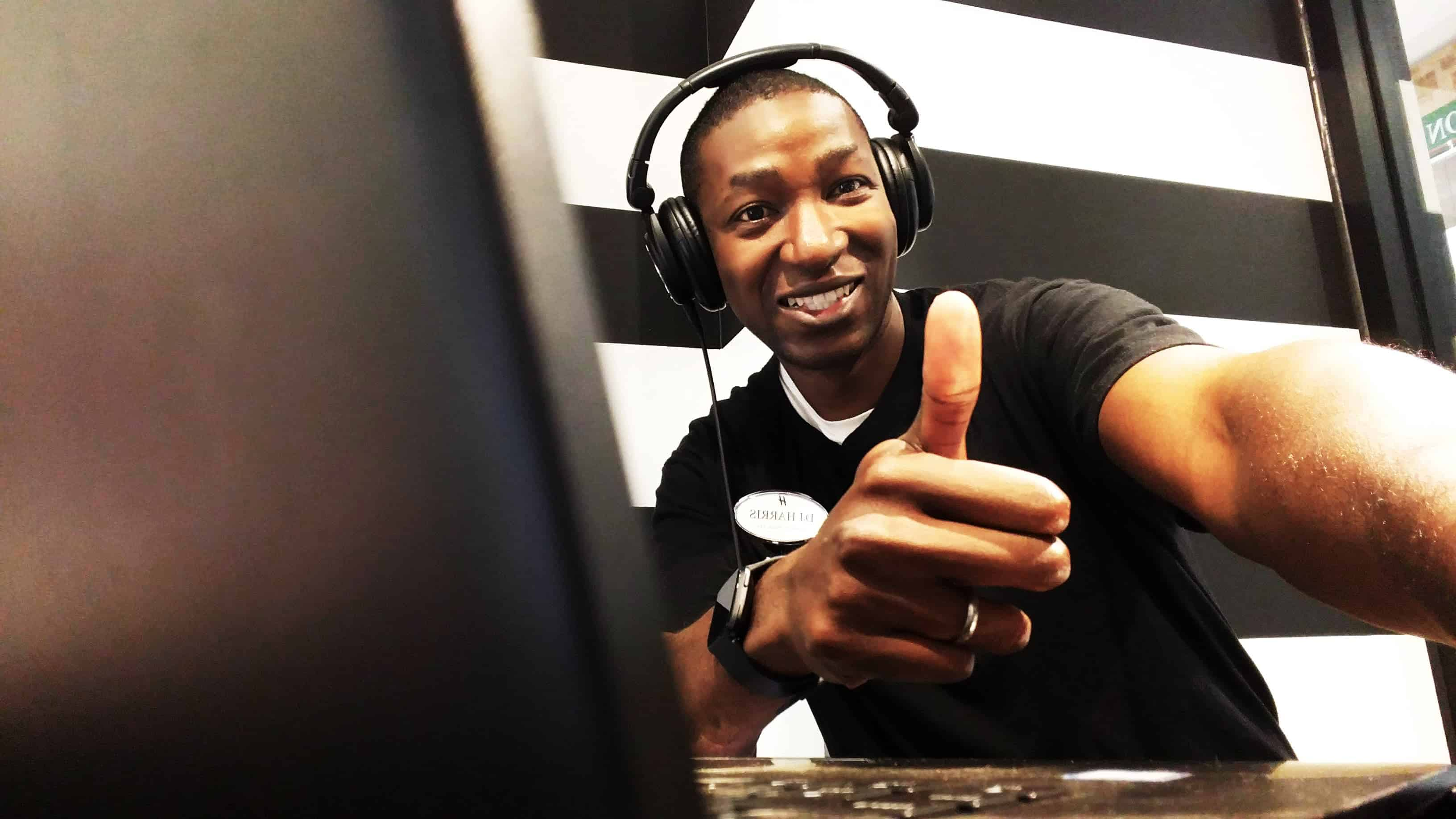 An image of DJ Harris giving a thumbs up to the camera as he is mixing jamming out during a DJ session in Sephora for a Too Faced Comsetics Party