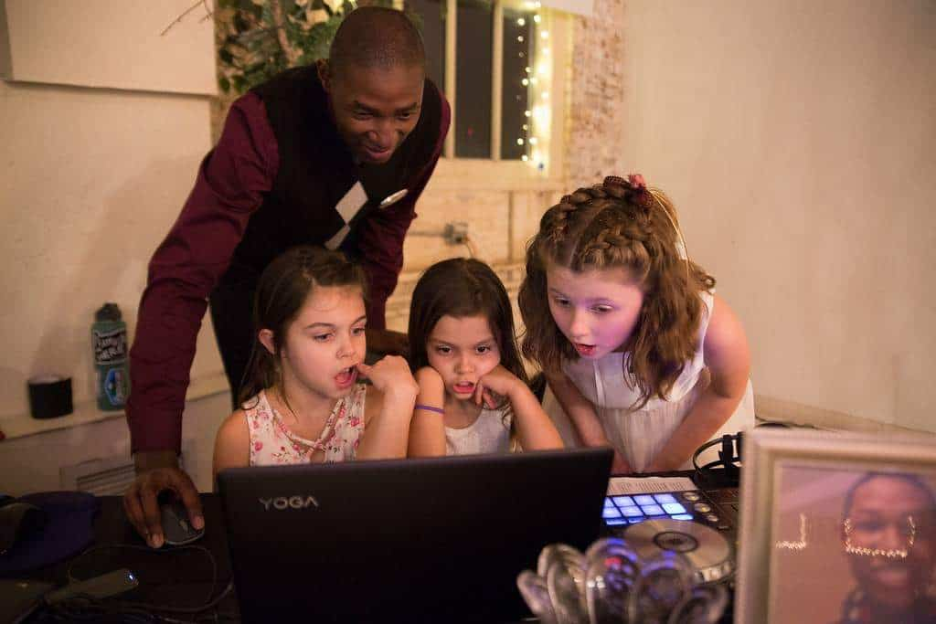 An image of DJ Harris with three kids who are getting a lesson on how to select the next song and transition between songs using the DJ controller. This image was captured during a wedding reception.