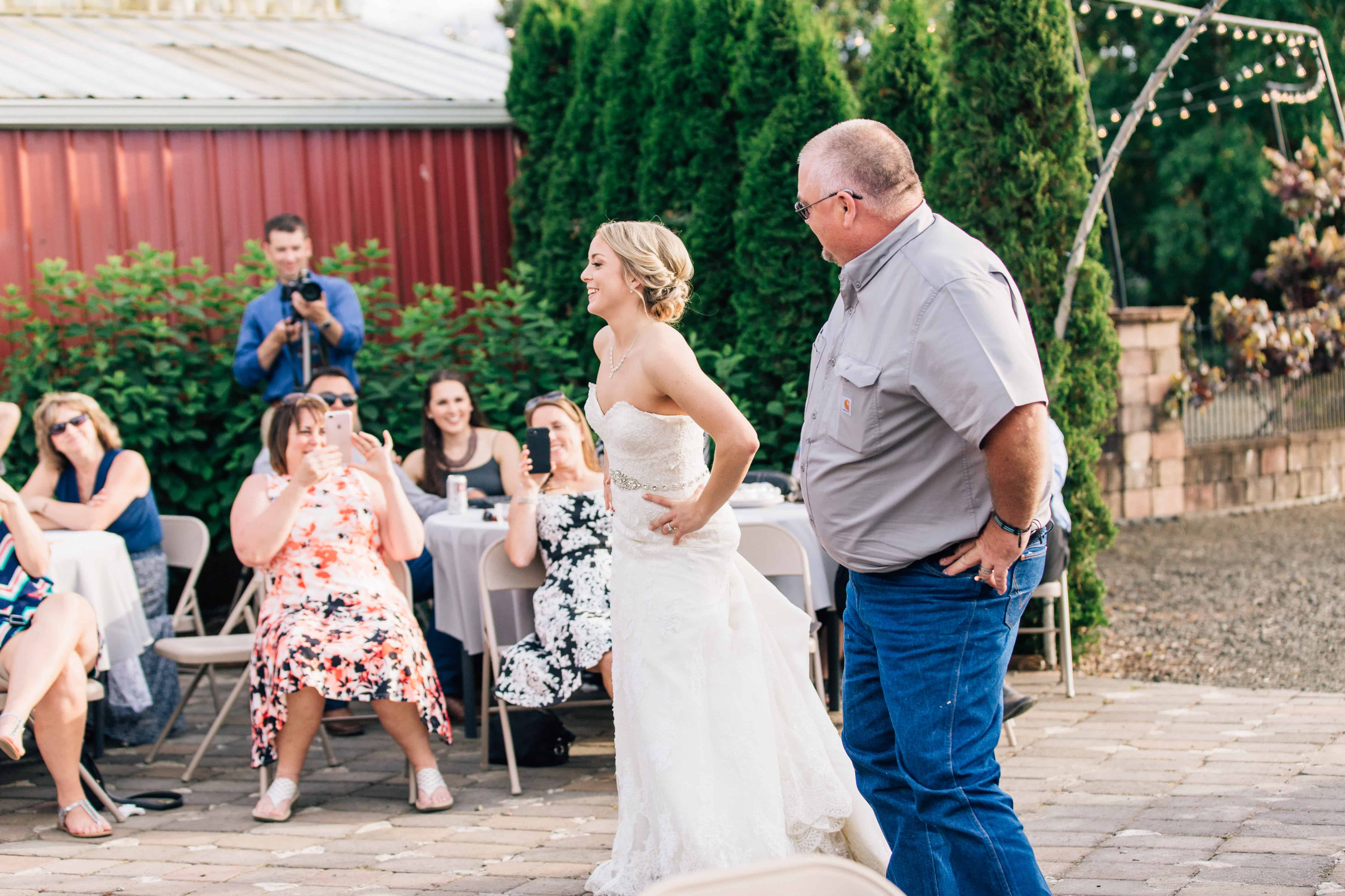 An image of a wedding scene where the Father of the Bride and the Bride are doing a fun dance for their Father and Daughter Dance. Wedding Guests can be seen in the background.