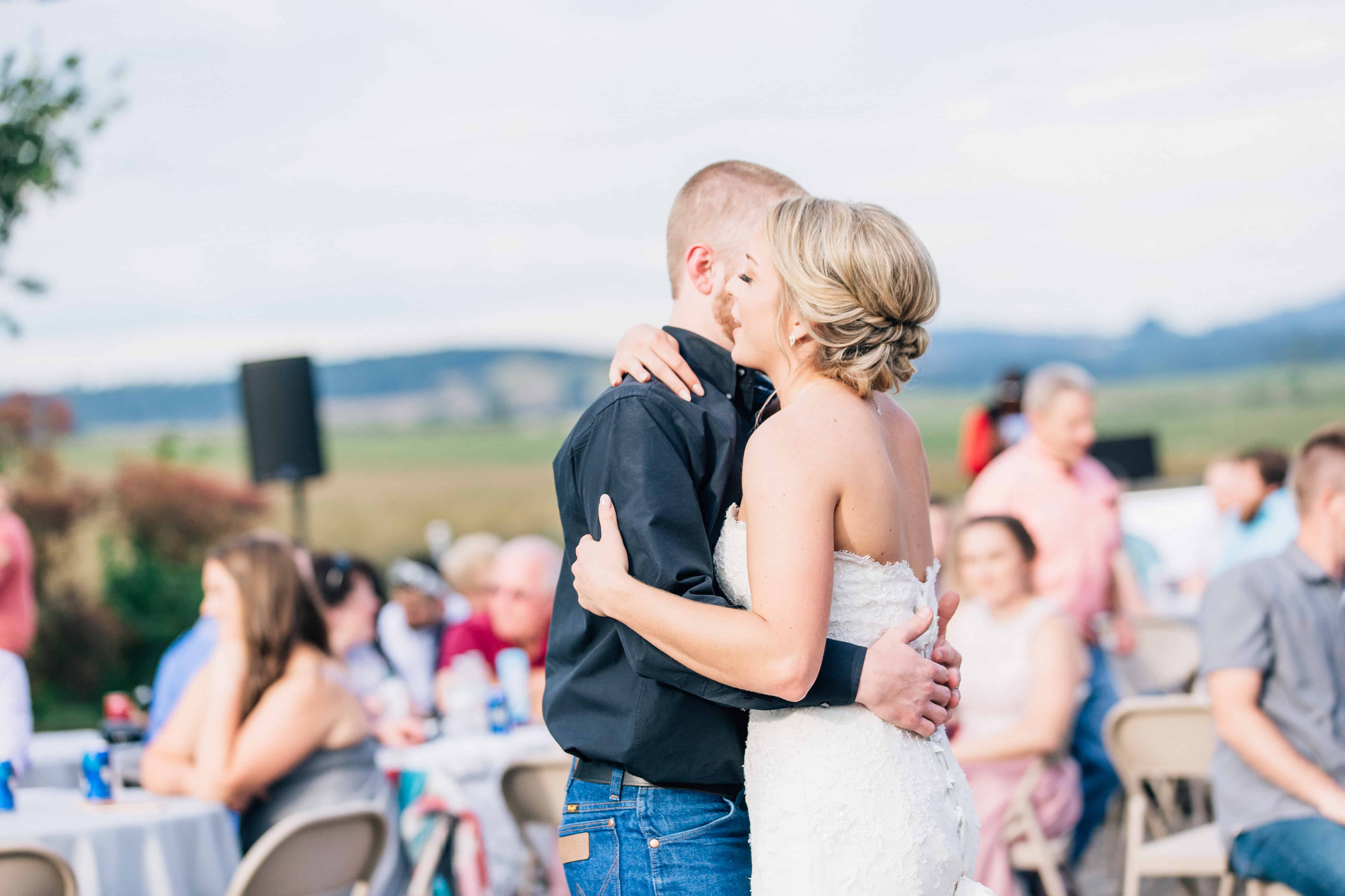 An image of a newlywed couple during their first dance at their wedding. The bride is in a strapless white gown. The groom is in blue jeans with a black button down dress shirt. Wedding Guests can be seen in the background of the picture.